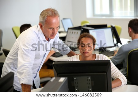 Teacher with student working on desktop computer - stock photo