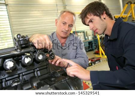 Teacher with students in mechanics working on bike - stock photo