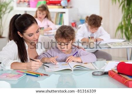 Teacher with thee young pupils - stock photo