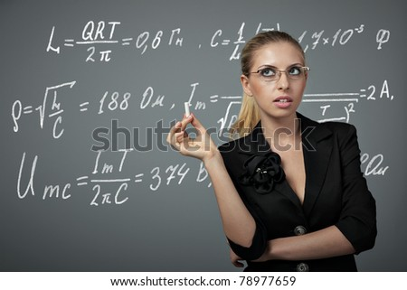 Teacher woman with chalk and writing physics formula