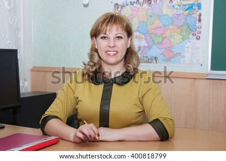 teacher working at the table in the classroom - stock photo