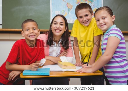 Teacher working with a group of students at the elementary school - stock photo