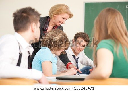 Teacher working with her students in a classroom - stock photo