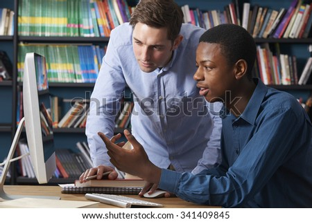 Teacher Working With Male Teenage Pupil At Computer - stock photo