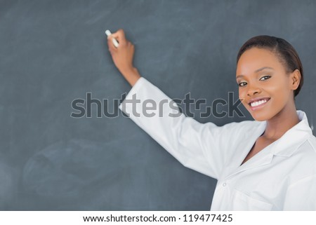 Teacher writing on a blackboard while looking at camera in a classroom