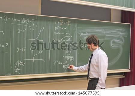 Teacher writing on a chalkboard - stock photo