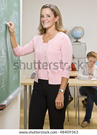 Teacher writing on blackboard - stock photo