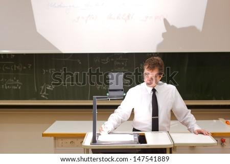 Teacher writing on projector - stock photo
