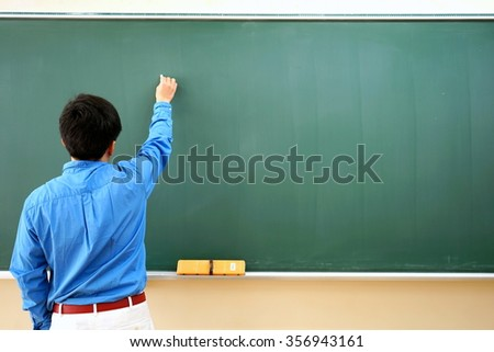 teacher writing on the chalkboard during the lecture in the school - stock photo