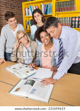 Teachers and students discussing over book at desk in college library - stock photo