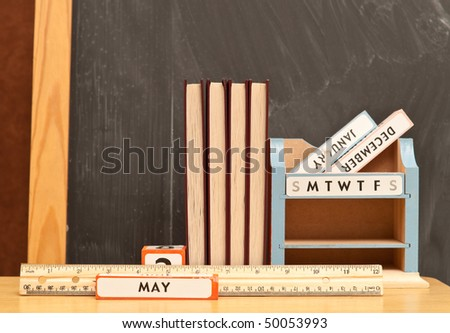 Teachers Desk with Books and Chalkboard Background