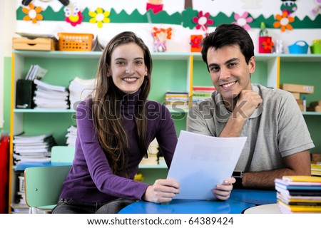 Teachers or teacher and parent having a discussion in classroom - stock photo