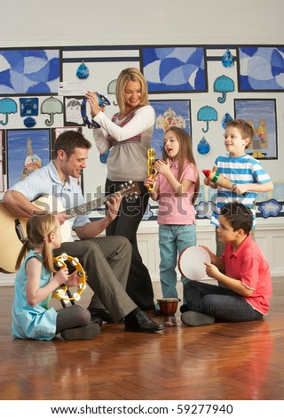 Teachers Playing Guitar With Pupils Having Music Lesson In Classroom - stock photo
