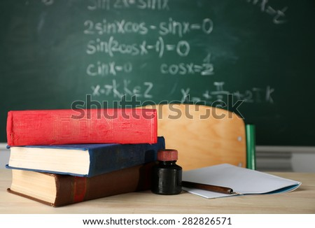 Teachers workplace  on blackboard background - stock photo