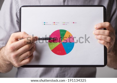 Teaching. Close-up of businessman holding clipboard with diagram and pointing at it