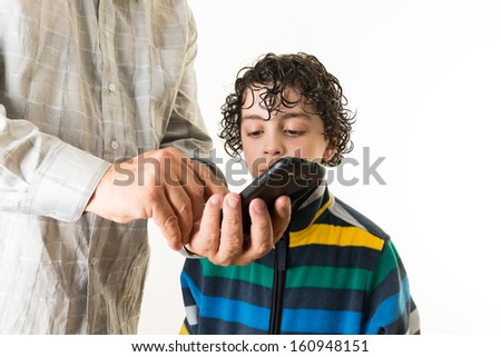 Teaching the new generation about technology. Father shows his son the different features of a smart phone. Education in gadgets over a white background