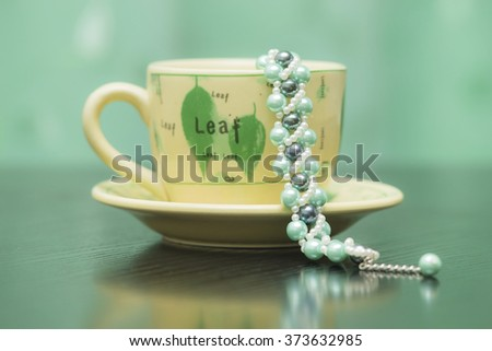 Teacup and a handmade bracelet - stock photo