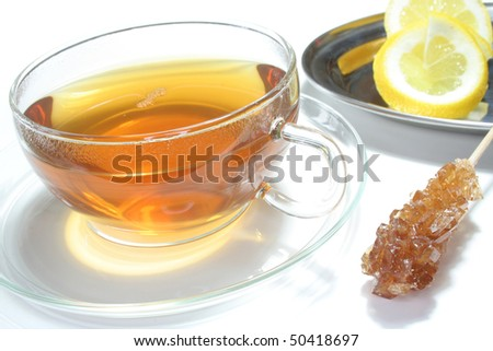 Teacup with lemon tea and fresh lemon slices on white background