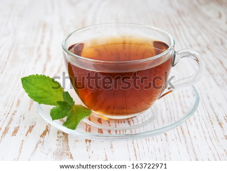 Teacup with mint leaves on a wooden background