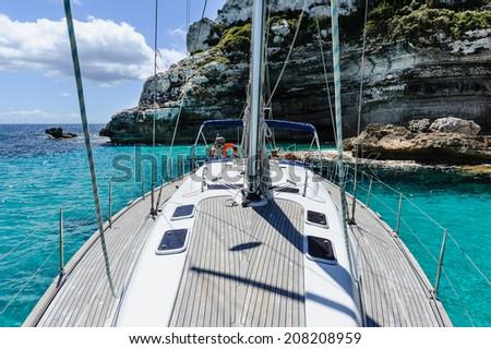 Teak deck of cruising sailing boat on anchor - stock photo