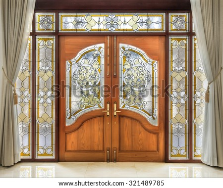 Teak wooden door with frosted glass interior. - stock photo