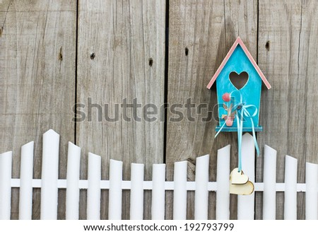 Teal blue birdhouse with wooden hearts hanging over white picket fence - stock photo
