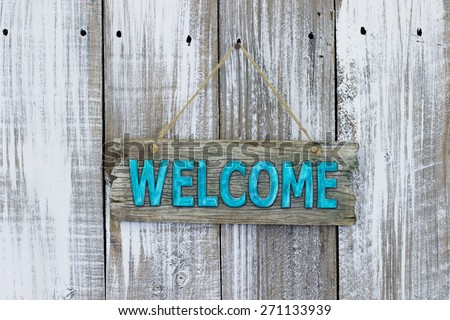 Teal blue welcome sign hanging on white painted weathered wood background - stock photo