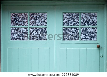 Teal Door with Flowery Windows, A delightful double windowed door painted teal with flowery laminate on the windows. - stock photo