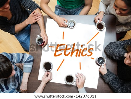 Team brainstorming over a poster on a table with ethics written on it - stock photo