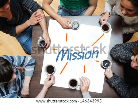 Team brainstorming over a poster on a table with mission written on it