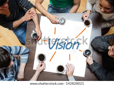 Team brainstorming over a poster on a table with vision written on it - stock photo