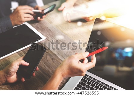 Team business meeting presentation. Hand businessman working new start up project in modern office.Laptop computer and digital table and smart phone on wood table, Sun flare effect photo          - stock photo