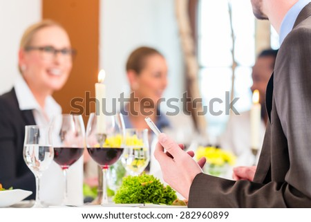 Team having business lunch in restaurant toasting with red wine to celebrate - stock photo