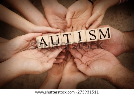 Team Holding Building Blocks spelling out Autism - stock photo