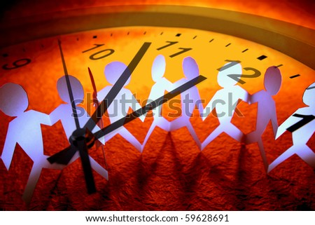Team holding hands and clock - stock photo