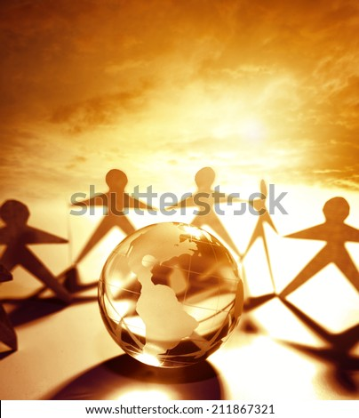Team holding hands behind globe - stock photo