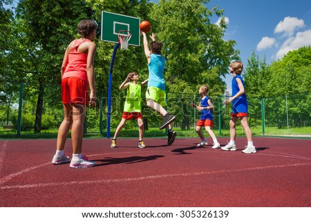 Team in colorful uniforms playing basketball game - stock photo