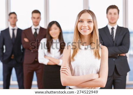 Team in the office. Young blond businesswoman standing in the foreground smiling and holding her arms crossed, her team of co-workers in the background