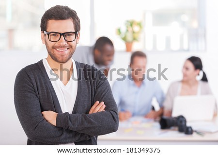 Team leader. Handsome young man in glasses keeping arms crossed and smiling while three people working on background - stock photo