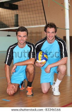 Team mates kneeling with volley ball on indoor court - stock photo