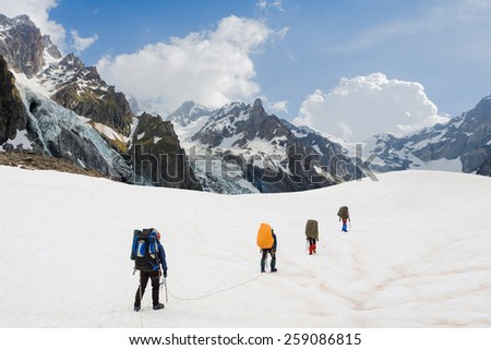 Team of alpinists crossing a glacier - stock photo