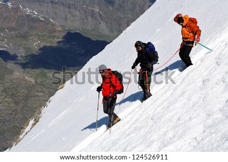 Team of alpinists descending an icy slope - stock photo