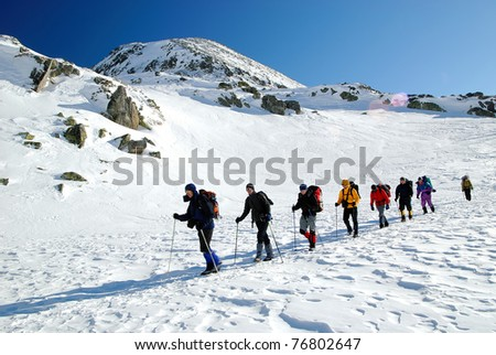Team of alpinists traversing an iced lake - stock photo