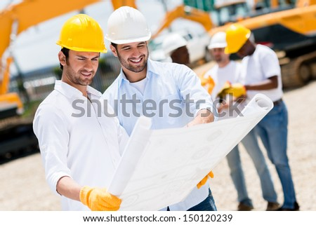 Team of architects at a building site looking at blueprints - stock photo