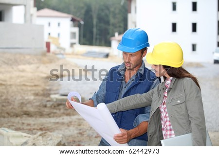 Team of architects checking plans on site - stock photo