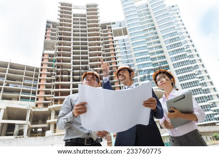Team of architects comparing housing project with the building - stock photo
