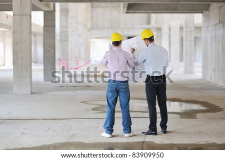 Team of architects people in group  on construciton site check documents and business workflow - stock photo