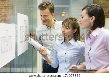 Team of architects working in office on construction project - stock photo