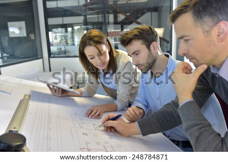 Team of architects working on construction project - stock photo