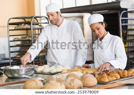 Team of bakers preparing dough and pastry in the kitchen of the bakery - stock photo